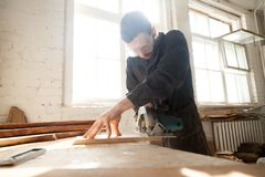 Woodworker works on local lumber production Royalty Free Stock Image