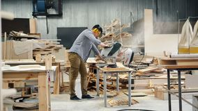 Woodworker busy sawing wood with circular saw standing in workshop. Woodworker young man is busy sawing wood with circular saw standing in workshop wearing stock footage