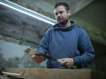 Woodworker z brodą piłuje drewnianego promień z ręką zobaczył cieśla piłuje kawałek drewno obraz stock
