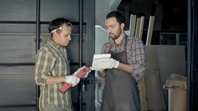 2 woodworkers обсуждая процесс делать изделия из древесины Стоковая Фотография RF