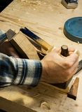 Woodworkers hands on an old fashion hand plane. Wit some other tools on the workbench Stock Photo