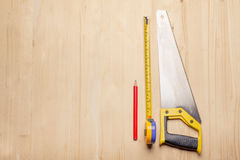 Woodworkers tools - ruler, saw, pencil on wooden table Royalty Free Stock Photography