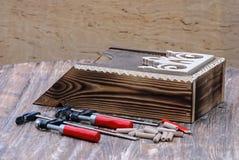 woodworking Ainda vida das braçadeiras, dos pinos de madeira, do lápis e da caixa postal de madeira Imagens de Stock