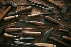 Woodworking background with vintage hand tools. In a flat lay full frame view with screwdrivers, hand saw, snips, hammer and mallets stock photography