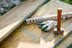 Woodworking Construction Tools on Planks of Wood. Looking Down at Wooden Mallet, Level and Gloves, Woodworking and Construction Tools on Planks of Wood Outdoors Royalty Free Stock Photo