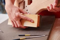 Woodworking with grind by carpenter. Using abrasive paper Royalty Free Stock Photos
