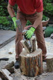 Woodworking man with a splitting wedge in the garden Stock Photos
