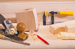 Woodworking plane with other tools on wooden board Stock Photo