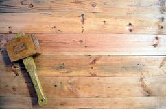 Woodworking tools -  Wooden Mallet. A wooden Mallet on a wood background. Background image showing a woodworking tool with place for captions and notes Stock Photo