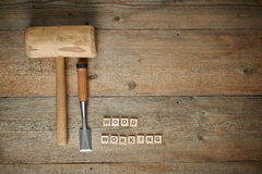 Woodworking word with mallet and chisel on wooden workbench, top Royalty Free Stock Photos