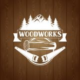 Woodworks label with wood log and saw. Emblem for forestry and lumber industry Stock Image
