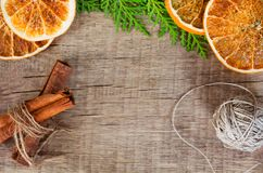 On a woody background, spices are laid out: lemon, cinnamon, cloves, tubby, anise and greens cypress branches.  Royalty Free Stock Photos