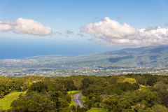 Woody hills, meadows and road with densely populated coast in th. E background, la Reunion island Stock Photography