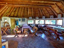Woody lunch room in a chalet in Montenegro. Travel destination. Summertime and holidaytime. Balkans. Ecology and natural life. Long table covers. Long wood royalty free stock photo