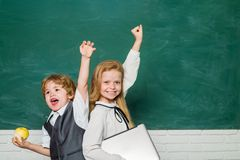 Woohoo. Cheerful smiling child at the blackboard. Schoolchild. Book school and kids. Classroom. School lessons. Yeah. Good work stock photo