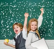 Woohoo. Cheerful smiling child at the blackboard. Schoolchild. Book school and kids. Classroom. School lessons. Yeah stock images