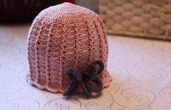 Wool cap for child  on a table. Crochet handmade hat. Stock Photo