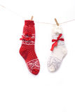 Wool Christmas socks, red and white, hanging on the white wall. Two pairs of wool Christmas socks, red and white, hanging on the white wall Stock Images