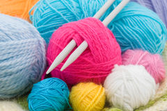 Wool clews. Colored wool clews with needles as background Royalty Free Stock Image