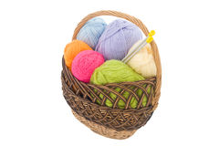 Wool clews  in  basket. Colored wool clews with needles in wicker basket Stock Photo