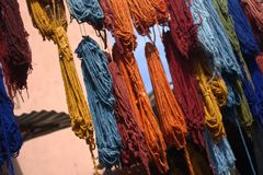 Wool and colored fabrics put to dry extended to a thread in the sun. Traveling for the colorful and fragrant oriental countries in homes and in old cities Stock Photos