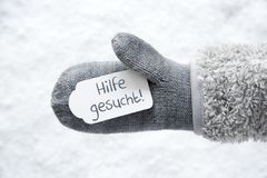 Wool Glove, Label, Snow, Hilfe Gesucht Means Help Wanted. Wool Glove With Label With German Text Hilfe Gesucht Means Help Wanted. White Snow Background Royalty Free Stock Image