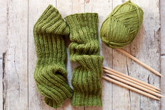 Wool green legwarmers, knitting needles and yarn Royalty Free Stock Images