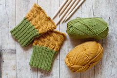 Wool green and yellow legwarmers, knitting needles and yarn Royalty Free Stock Photography