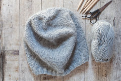 Wool grey hat, knitting needles and yarn Stock Image