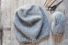 Wool grey hat, knitting needles and yarn Stock Image
