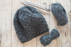 Wool grey hat, knitting needles and yarn Royalty Free Stock Photo