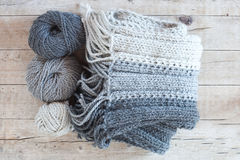 Wool grey scarf and yarn. Closeup on wooden background stock photography