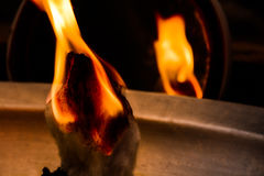 A Wool Grin Set on Fire in a Dramatic Way. Photo Contains a Piece of Wool Grin placed on a steel Tub which has Mustard Thrown on it. And a Mirror is placed Royalty Free Stock Photography