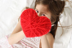 Wool heart. Lying little girl with the red wool heart Stock Photography