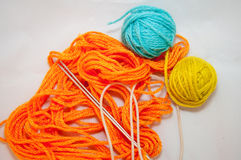 Wool, socks and knitting needles. knitwork. Orange, blue and yellow wool balls and knitting needles on white background Royalty Free Stock Images