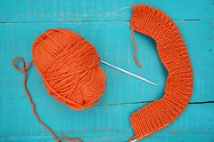 Wool and knitting needles. Orange yarn and knitting needles on blue background Stock Photography