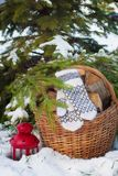 Wool mittens on the basketful of firewood near snowy Christmas-tree and a red lantern Stock Photo