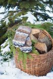 Wool mittens on the basketful of firewood near snowy Christmas-tree Royalty Free Stock Images