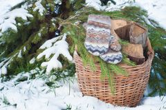 Wool mittens on the basketful of firewood near snowy Christmas-tree Royalty Free Stock Image