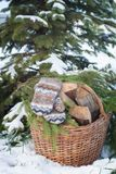 Wool mittens on the basketful of firewood near snowy Christmas-tree Stock Photo