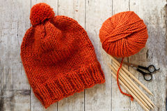 Wool orange hat, knitting needles and yarn Royalty Free Stock Image