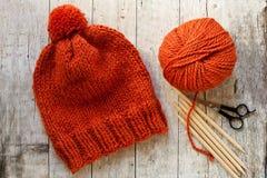 Wool orange hat, knitting needles and yarn Royalty Free Stock Image