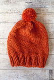 Wool orange pompom hat. Closeup on wooden background Royalty Free Stock Photography