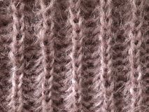 Wool pink knitwear for winter clothes. Wool knitwear for winter clothes. Pink background with the texture of warm knitwear royalty free stock photography