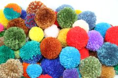 Wool pompoms. Pompoms made with colored wool on white background for handicrafts Stock Image