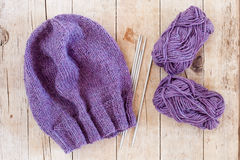 Wool purple hat, knitting needles and yarn Royalty Free Stock Image