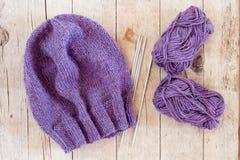 Wool purple hat, knitting needles and yarn Royalty Free Stock Image