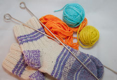 Wool, socks and knitting needles. knitwork. Orange, blue and yellow wool balls and knitting needles and socks on white background Stock Photo