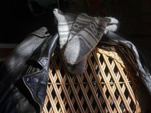 Wool socks and leather jacket. Hanging on a chair stock images