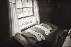 Wool Socks Window. A monochrome photo of some old fashioned handmade wool socks laying on a trunk in front of a window with sheer curtains at Old World Wisconsin Stock Photography